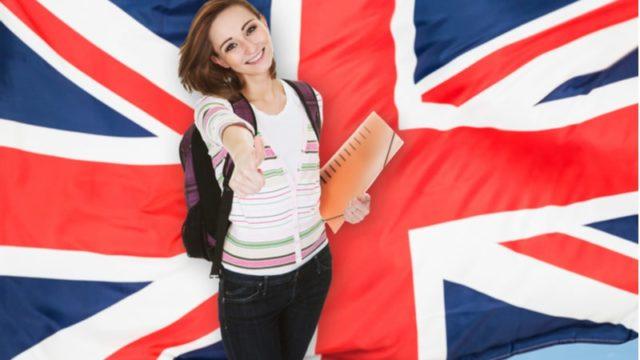 イギリスの国旗を背景にこちらを見て笑顔でサムアップしている外国人女性