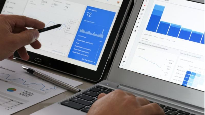 タブレットとノートパソコンの画面を見比べてwebサイトのアクセス分析をしている人