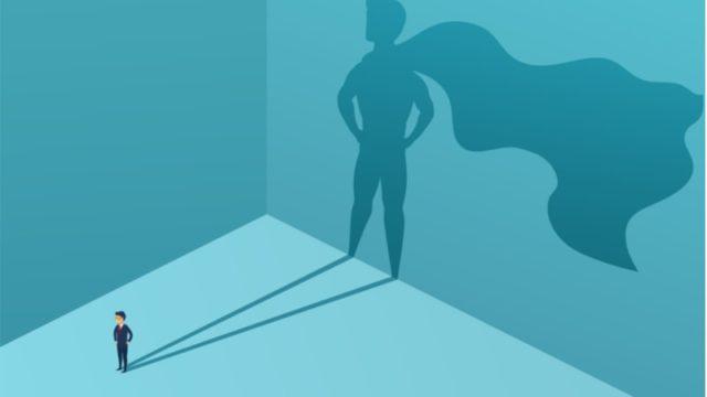 壁に映るヒーローの姿をした男性の影