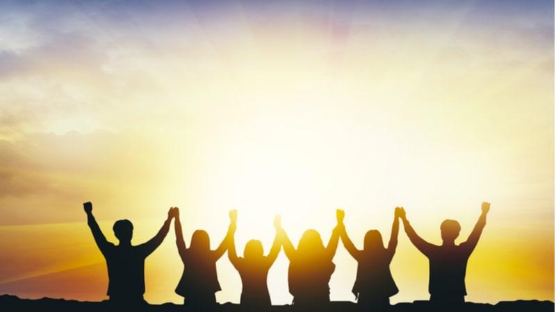 夕日を背に手を繋いでバンザイをする6人の男女