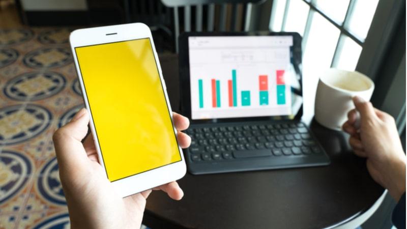 机の上にあるノートパソコンと左手に持ったスマートフォン