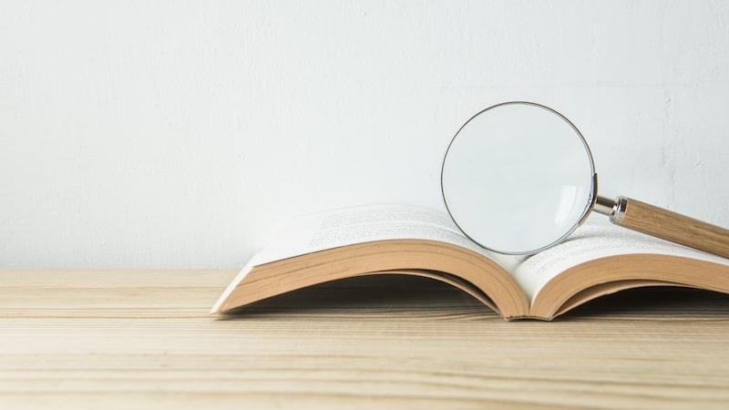 開かれた本の上に置かれた虫めがね
