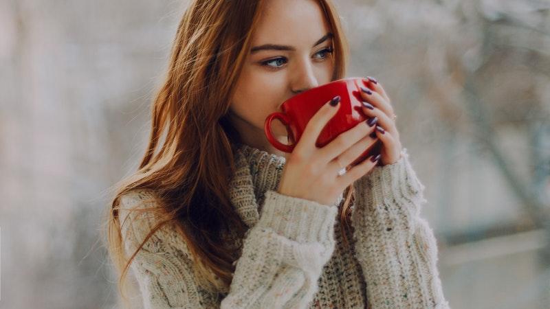 赤いマグカップを両手で持ち温かい飲み物を飲む外国人の女性