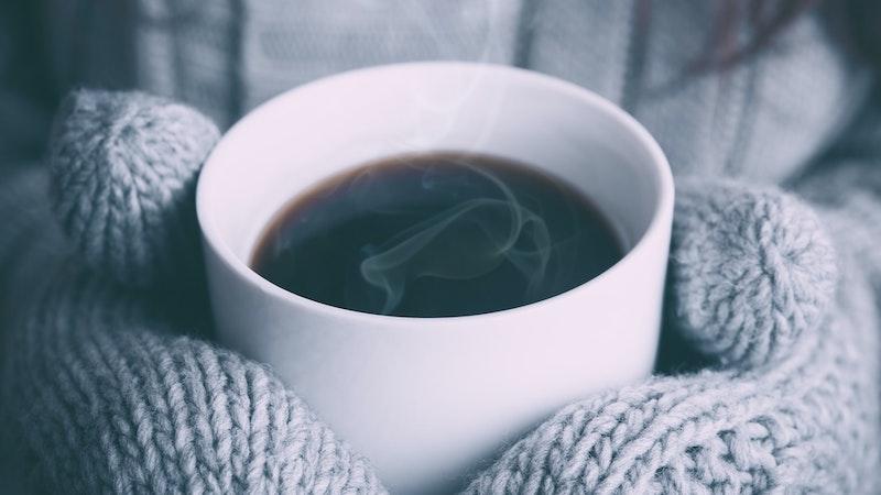 毛糸の手袋をしてホットコーヒーの入ったマグカップを持つ女性