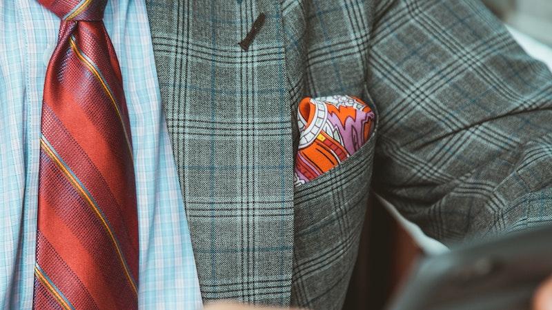 スマートフォンを操作しているスーツを着てネクタイをした男性