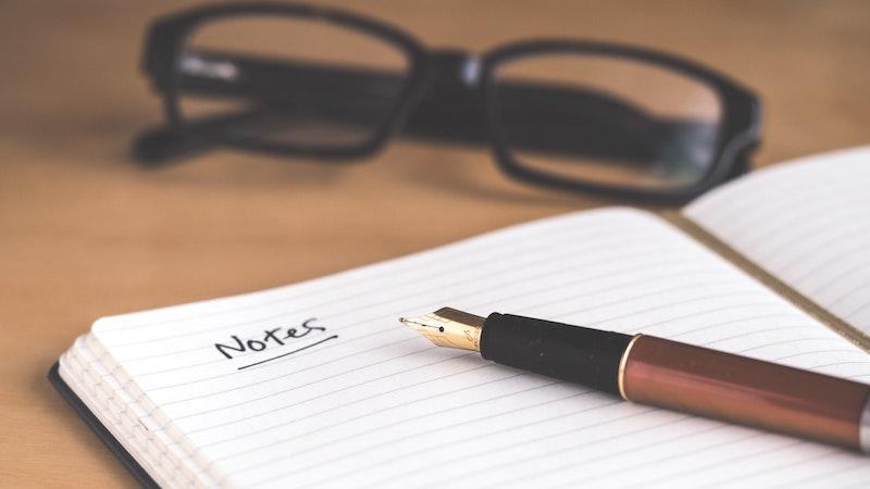 机の上に置かれたノートと万年筆と黒いメガネ