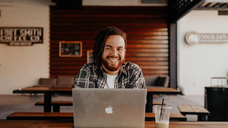 開かれたノートパソコン越しにこちらに微笑みかける男性