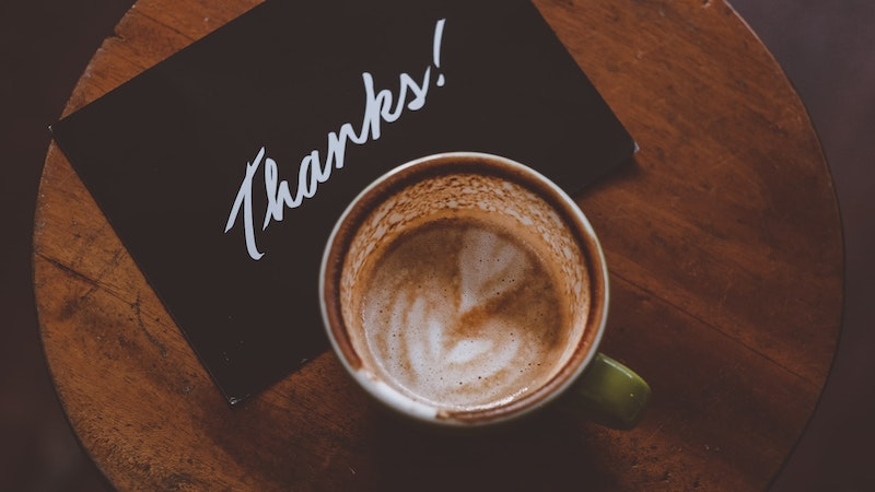 テーブルの上に置かれたコーヒーとthanksと書かれたカード