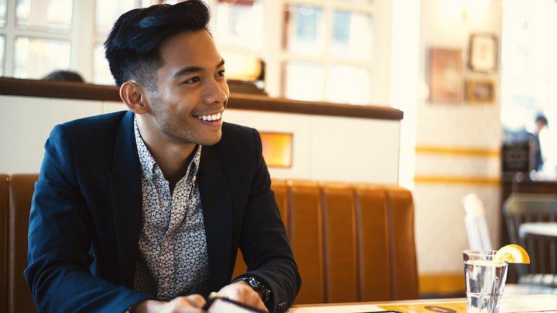 笑顔で微笑む紺のジャケットを着た男性